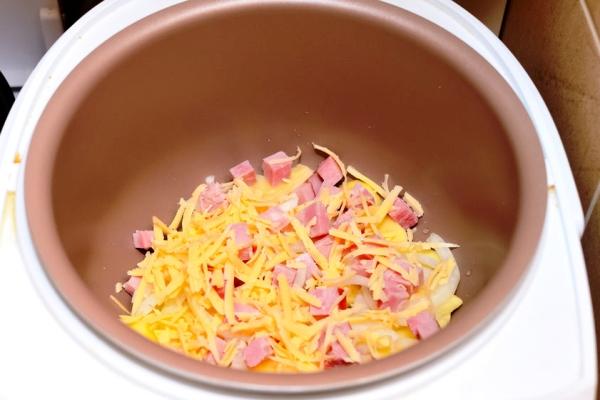 Помещаем в кастрюлю картошку и ветчину