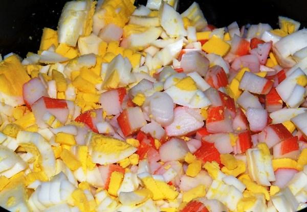 Добавляем в салат из крабовых палочек с кукурузой резанные яйца