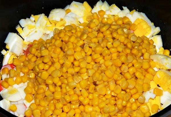 Добавляем кукурузу в салат из крабовых палочек с рисом